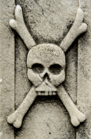 swashbuckler: skull and cross bones on lateral of building in cementery Stock Photo