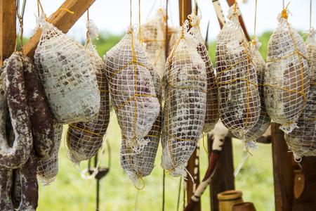 jamones: jamones y embutidos colgando de un poste en venta