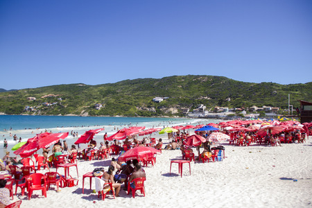 going for it: Beach on the coast of Brazil in Arraial do Cabo, the sand is white, the sea is turquoise and is crowded. It has red umbrellas and tables and chairs of the same color. People are sitting or going to get into the sea for swimming or playing around. Editorial