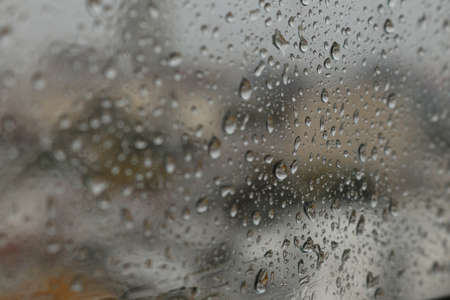 Raindrops on a misted glass with a soft multi-colored background on a rainy day Stock fotó