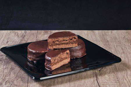 Chocolate alfajor on black plate on a wooden table and dark background. Selective focus. Copy space