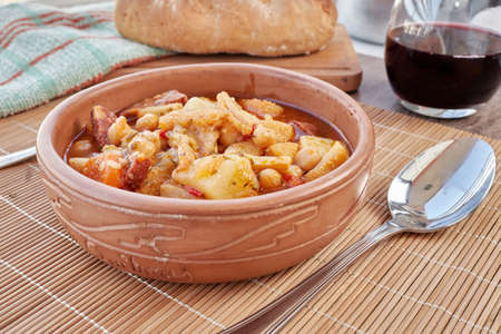 Plate of the typical cuisine of Madrid, Spain. Mondongo a la espanola or cayos a la espanola. Made with tripe, meat, chorizo, chickpeas and potato in a vegetable and tomato sauce. Presented in an earthenware bowl, on a wooden table and various additional details such as wine, bread and others. Aerial view. at 45 degrees.