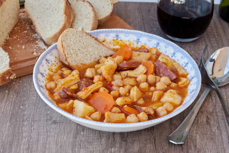 Plate of the typical cuisine of Madrid, Spain. Mondongo a la espanola or cayos a la espanola. Made with tripe, meat, chorizo, chickpeas and potato in a vegetable and tomato sauce. Presented on a white vintage plate with blue accents on a wooden table and various additional details such as wine, bread and others. Aerial view. view at 45 degrees. Foreground