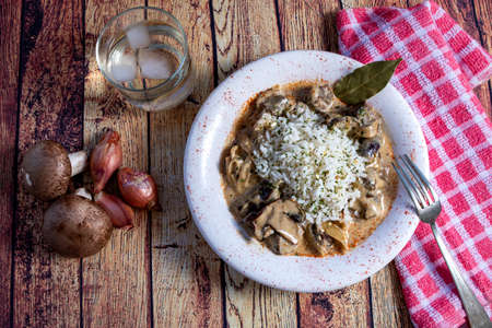 Mushroom beef stroganoff, with cremini and champignons, in a frying pan, shot from above, cenital view, on a dark rustic texture with a place for text