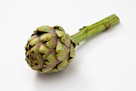 One organic artichokes with a piece of stem on a white surface. 写真素材