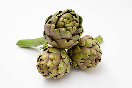 Three organic and fresh artichokes with a piece of stem on a white surface.