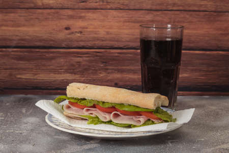 Ham, tomato and lettuce sandwich on a slab plate on a rustic background