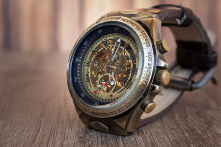 Steampunk style wristwatch made of bronze, steel, navy blue inner ring and brown leather mesh on a wooden board. You can see the internal machine of the clock. Stock Photo