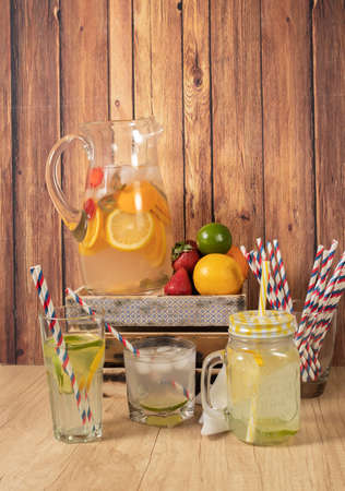 Large glass pitcher with citrus flavored water and homemade lemonade. Glass or jar with drink, lid and straw. Ideal for hot summer days. Concept of freshness, health and non-alcoholic drinks.