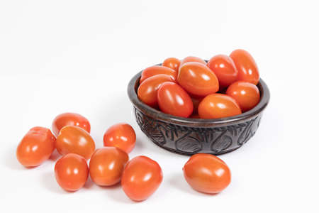 Cherry tomatoes in an African ebony wood bowl on a white background. Some cherry are fallen on the table. concept vegetable, cooking,