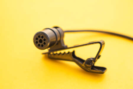 Lavalier or lapel microphone on a yellow surface, very close-up. The details of the grip clip or bra. Stock Photo