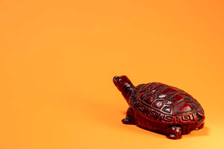 Small sculpture of a terra cotta colored African tortoise walking.