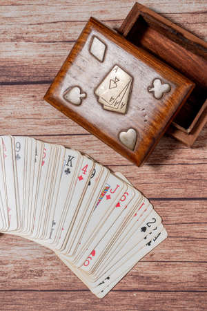 Wooden box for poker cards and cards fanned out on a wooden table. Vertical view