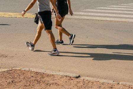 Runner feet running on road closeup on shoe. Peoples fitness sunrise jog workout welness concept.