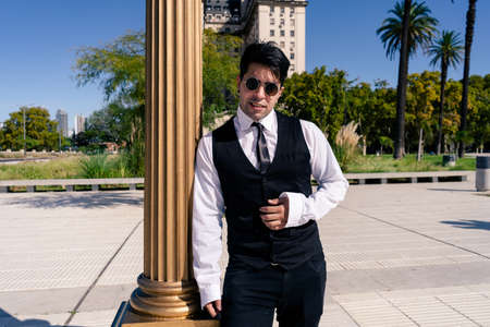 Young Latino entrepreneur leaning on an old column of light in a plaza. Reklamní fotografie