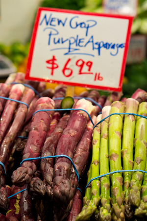 Purple and Green Asparagas wrapped in bunches for sale at a market