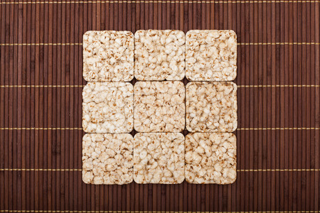 square composition: Square composition of nine crunchy rye crispbreads on bamboo napkin