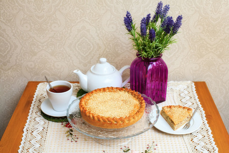 meat pie: Meat pie with sesame, teapot, cup of tea. Composition on table