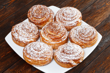 Sweet roll buns with shugar powder on wooden table Stock Photo
