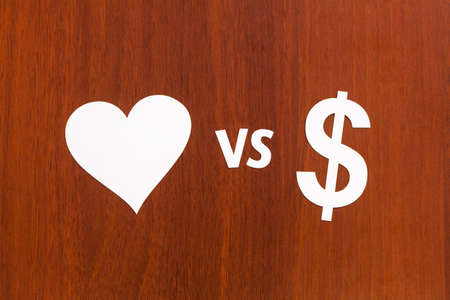 vs: Love vs money, paper signs. Abstract conceptual image. Wooden background Stock Photo