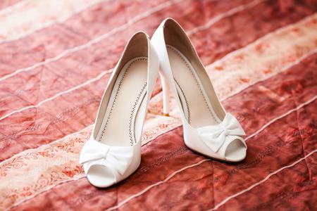 blanc élégant chaussures de mariage de mariée sur canapé rouge. concept de mariage