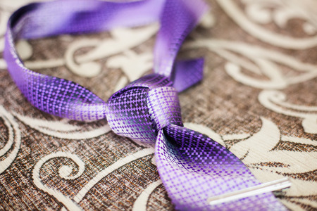Purple necktie with trinity tie knot on a sofa, close-up Stock Photo