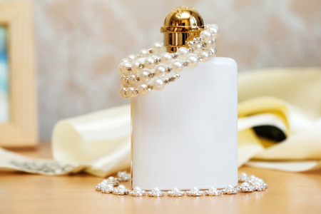 parfume: White bottle of wedding parfume with costume jewelry Stock Photo