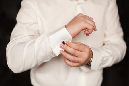 wrist cuffs: Elegant young fashion man fixing his cufflinks, closeup Stock Photo