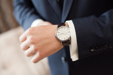 The groom in dark suit puts on a watch, close-up
