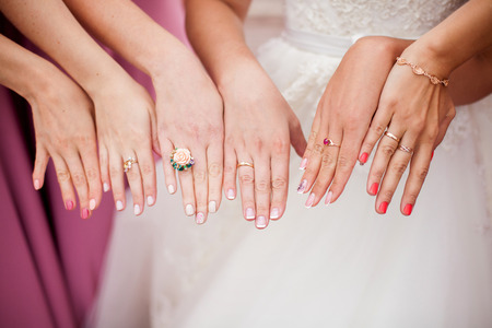 The bride and bridesmaids are showing their hands with rings. Marriage concept