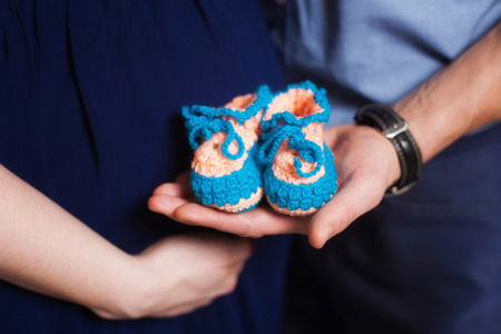 booties: Cute small blue knitted baby booties on hands. Pregnancy concept Stock Photo