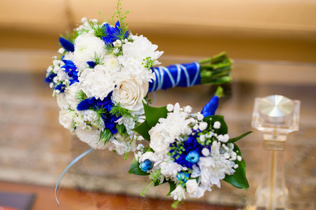 Beautiful blue and white wedding bouquet of roses on glass table