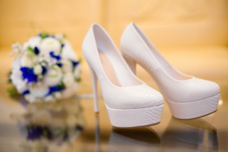 Chaussures de mariée blanches élégantes sur table en verre. Concept de mariage