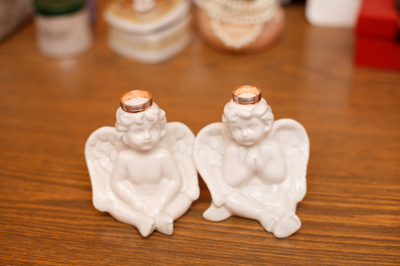 Two angels with golden rings on heads. Romantic composition for wedding day
