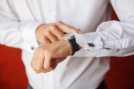 The groom in white shirt puts on a watch, close-up