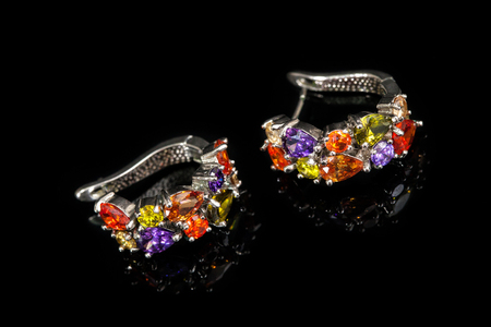 Earrings with colorful stones isolated on black glass, close-up Stock Photo