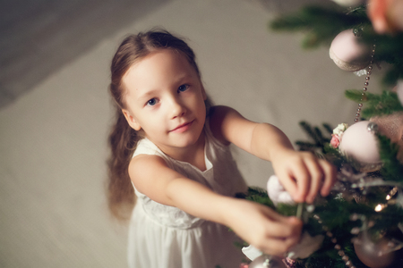 decorating christmas tree: Little girl decorating christmas tree, top view, vintage toned