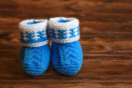 Blue hand made crochet baby booties on wooden background, copyspace, closeup Stock Photo