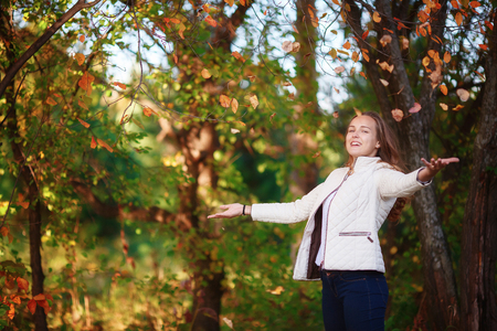 tosses: Young beautiful smiling teenager girl tosses colorful autumn leaves in park