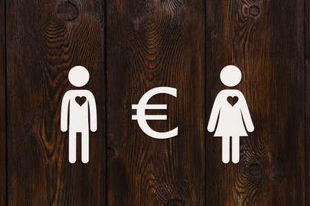love of money: Paper man, woman and euro sign on dark wooden background. Love relation and money concept. Abstract conceptual image
