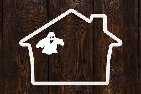 monsters house: Halloween holiday. Paper haunted house with ghost. Copyspace, abstract conceptual image. Dark wooden background Stock Photo
