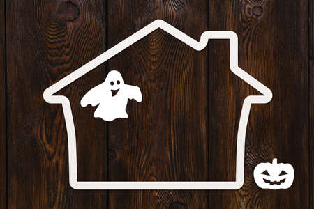 monsters house: Halloween holiday. Paper haunted house with ghost and pumpkin. Copyspace, abstract conceptual image. Dark wooden background Stock Photo