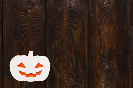 spectre: Halloween holiday. Paper smiling Grand Pumpkin. Dark wooden background, copyspace. Abstract conceptual image