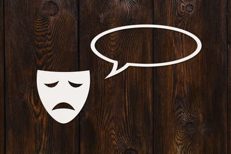paper mask: Paper sad mask is talking. Conversation. Emotion concept. Dark wooden background. Abstract conceptual image with copyspace Stock Photo