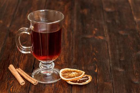ingridients: Compote or tea with fruit ingridients, dried orange, cinnamon. Dark rustic wooden background, copyspace