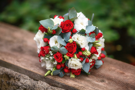 Beautiful wedding bouquet of roses on wooden background, red and white Stock Photo