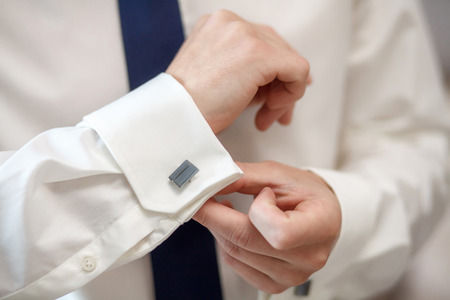 Elegant young fashion man fixing his cufflinks, closeup Stock Photo