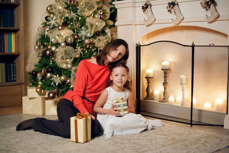 decorate: Little cute girl holding gifts and mother sitting near christmas tree. New year.