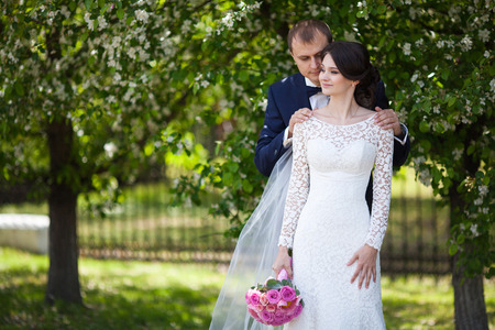 Young groom and bride with wedding bouquet in blooming garden