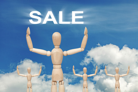 Wooden dummy puppet on sky background with word SALE. Abstract conceptual image